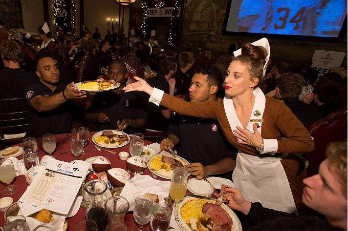 Stanford player receives a prime rib plate at 60th Lawry's Beef Bowl